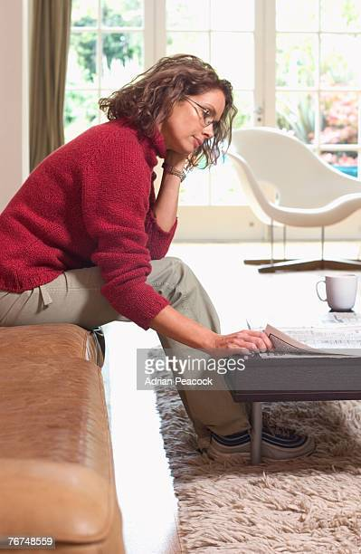 Woman sitting on a couch reading a newspaper