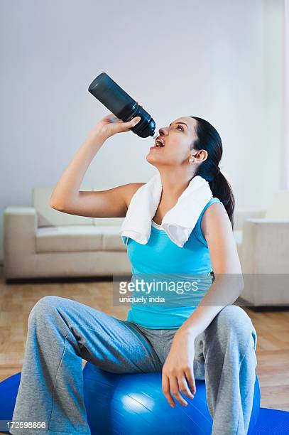 Woman sitting on a fitness ball and drinking water