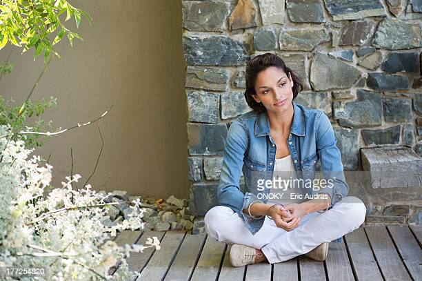 Woman sitting on a hardwood floor and day dreaming