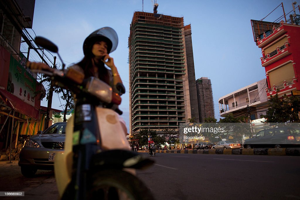 A woman sitting on a motorbike speaks on her mobile phone on Monivong Boulevard as the Gold Tower 42 project, developed by Yon Woo Cambodia Co., center, stands unfinished in Phnom Penh, Cambodia, on Sunday, Nov. 18, 2012. U.S. President Barack Obama arrives in Phnom Penh later today to join the Association of Southeast Asian Nations (Asean) East Asia Summit, which also includes leaders from Japan, South Korea, India, Russia, Australia and New Zealand. Photographer: Will Baxter/Bloomberg via Getty Images
