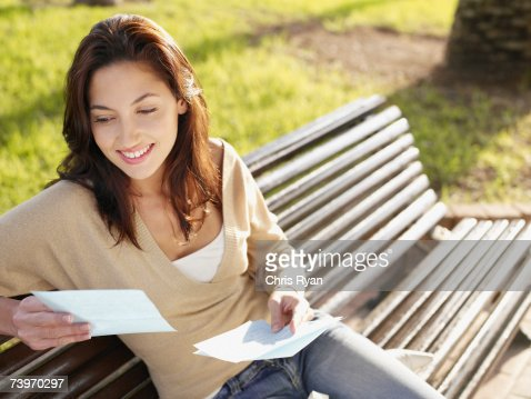 Woman sitting on a park bench reading a letter : Stock Photo
