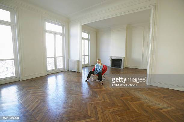 Woman Sitting on a Red Chair in a Large Empty Room