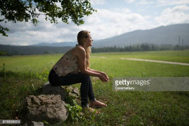 Woman Sitting on a Rock Leaning Foward in Countryside