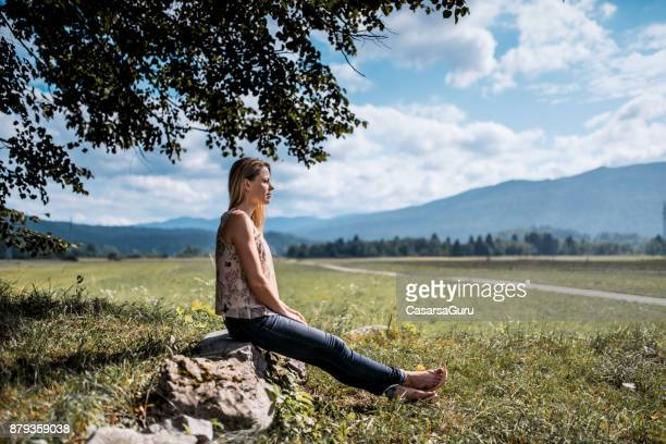 Woman Sitting on a Rock on Meadow Against Cloudy Sky