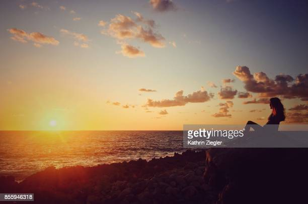 Woman sitting on a rock watching the sunset, northern Sicily