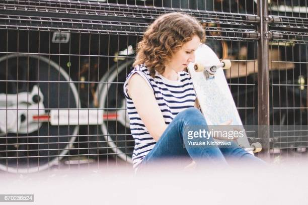 A woman sitting on a skateboard