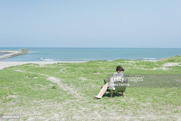 Woman sitting on a sofa at the beach