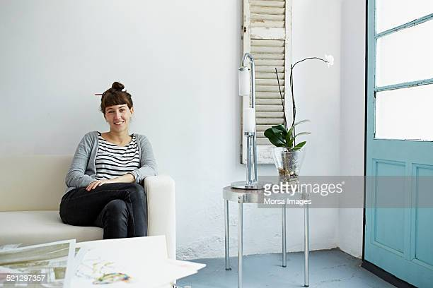 Woman sitting on a sofa with prints