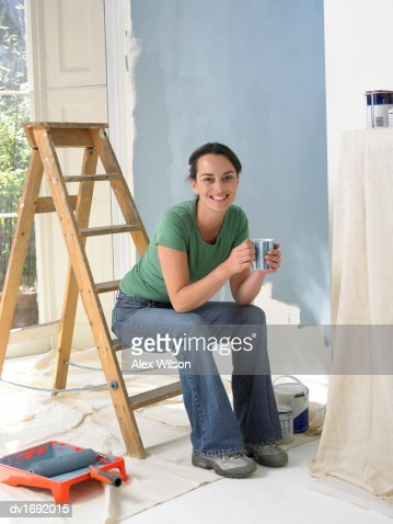 Woman Home Decorating woman covered in paint stock photo | getty images