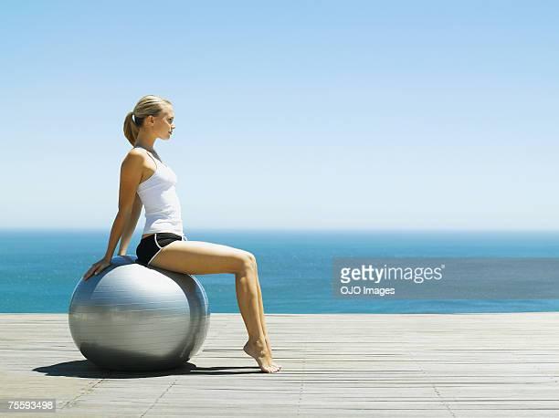 Mulher sentada sobre uma Bola de Exercício