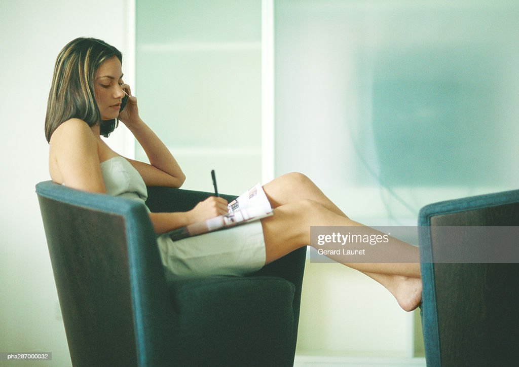 Woman sitting on arm chair with feet up using cell phone and taking notes  Stock Photo