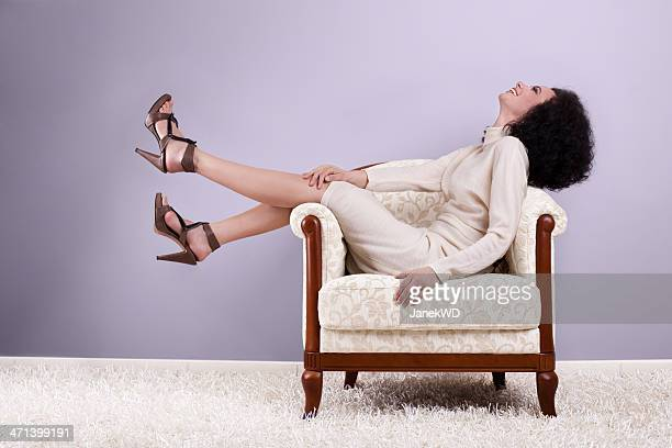 Woman sitting on armchair, profile, violet background
