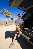 Woman sitting on back of SUV on desert road