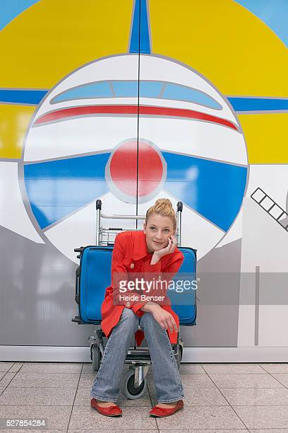 Woman sitting on baggage cart