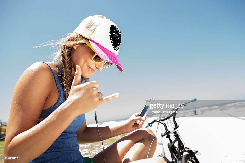 Woman sitting on beach and listening to music on smart phone : Stock Photo