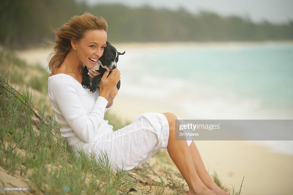 Woman sitting on beach, holding dog, smiling : Stock Photo