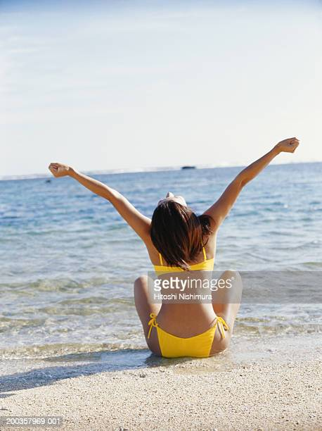 Woman sitting on beach with arms raised, rear view