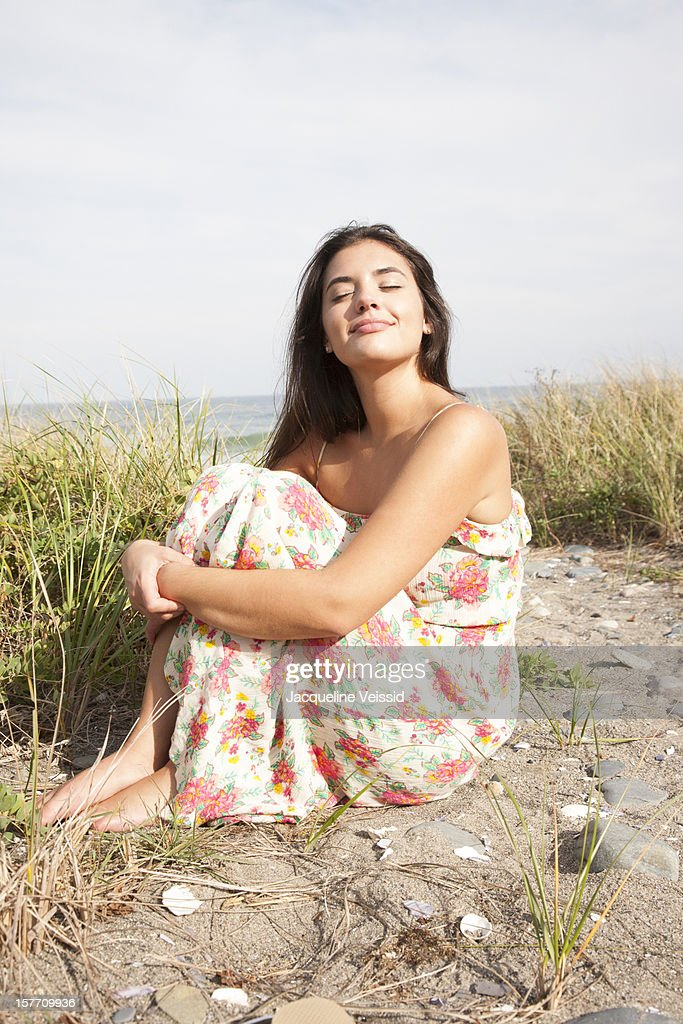 Woman sitting on beach with eyes closed : Stock Photo