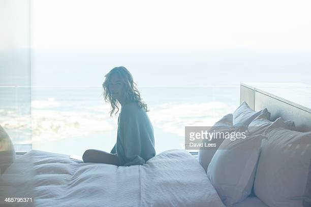 Woman sitting on bed by window