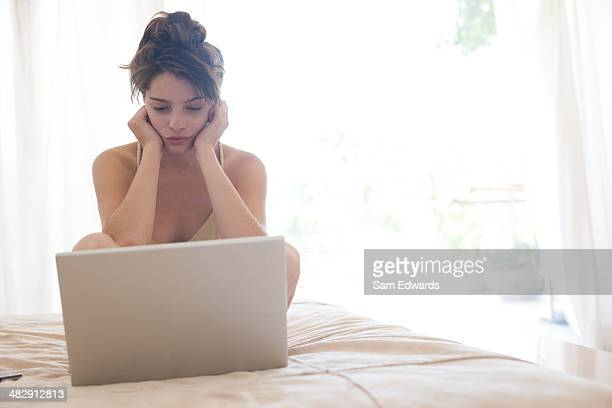 Femme assise sur le lit regardant un ordinateur portable