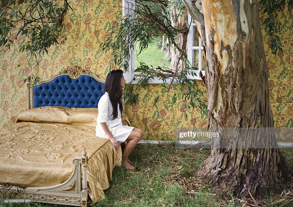 Woman sitting on bed, looking out of window : Stock Photo