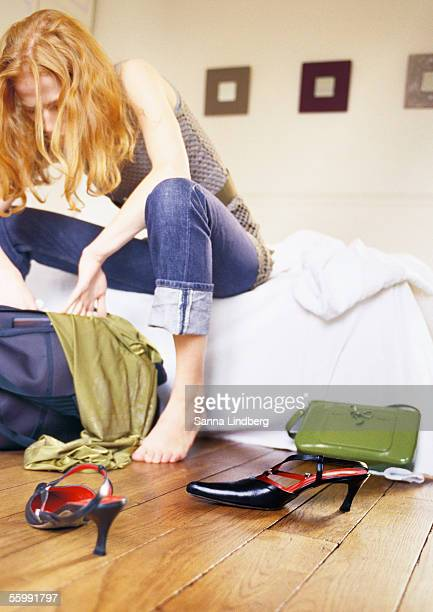 Woman sitting on bed looking through bag.