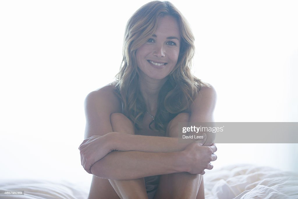 Woman sitting on bed : Stock Photo