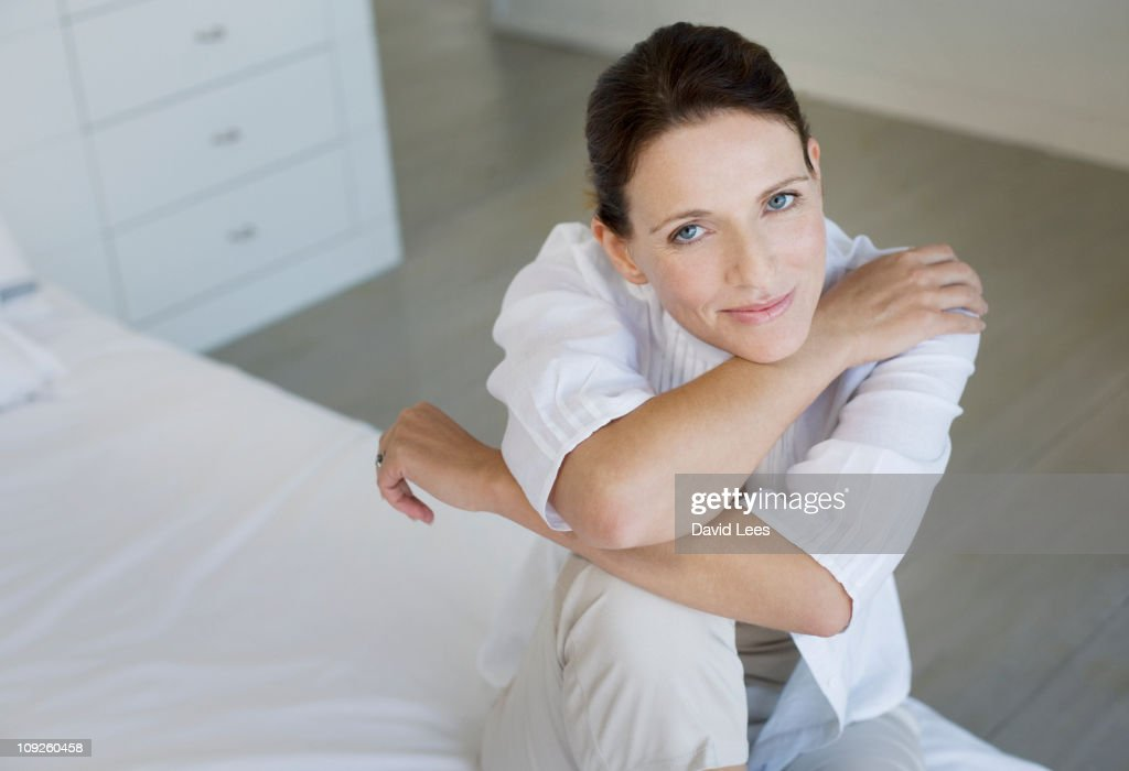 Woman sitting on bed, portrait, smiling : Stock Photo