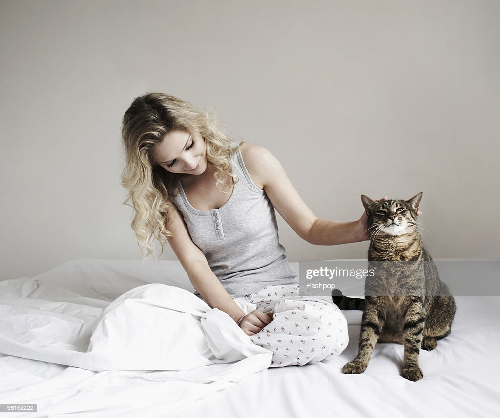 Woman sitting on bed stroking her cat : Stock Photo