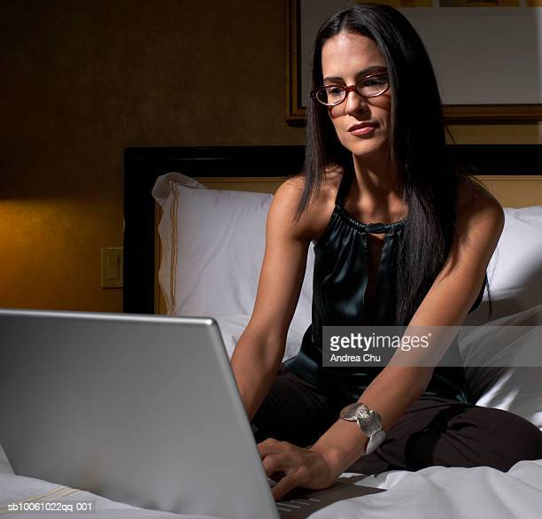 Woman sitting on bed, using laptop