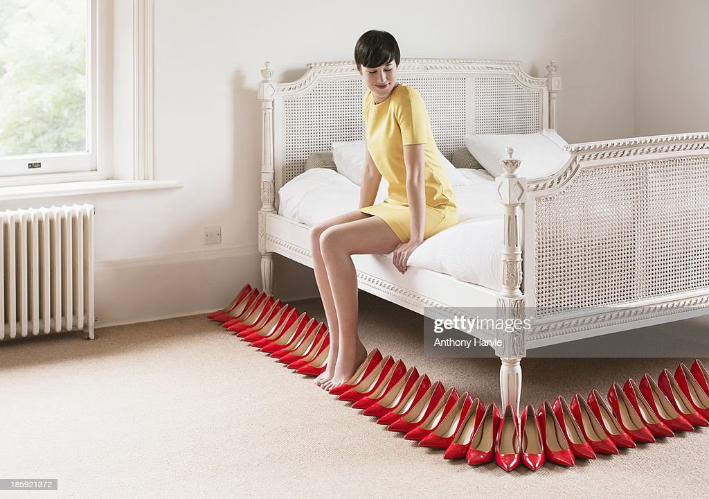 Woman sitting on bed with red shoes in a row