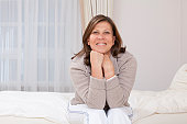 Woman sitting on bed,smiling at camera