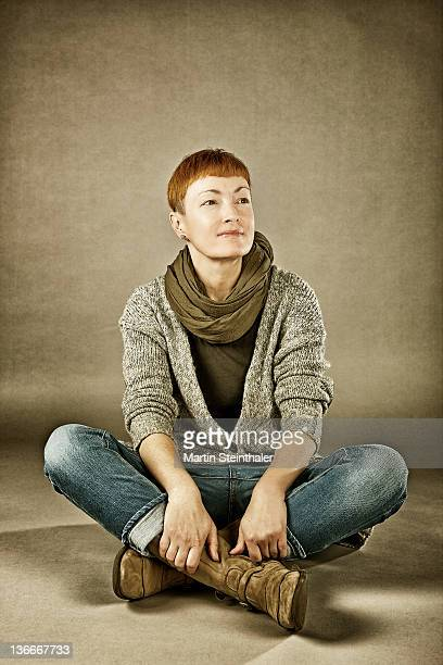 Woman sitting on beige background