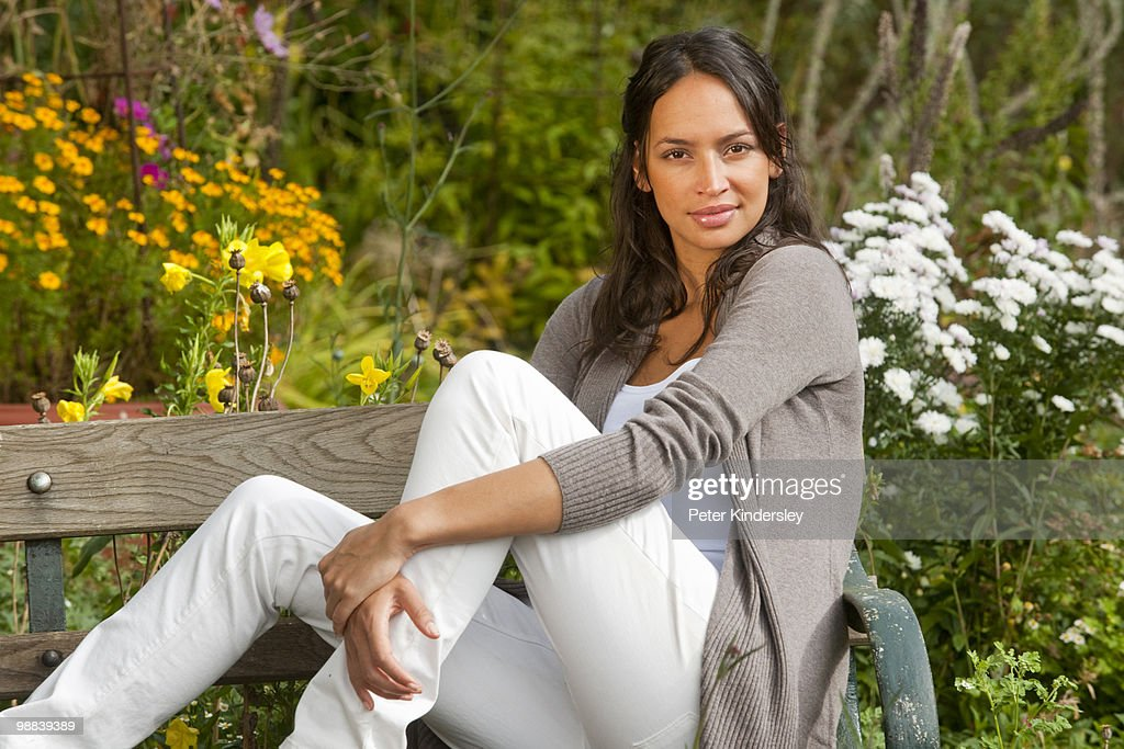Woman sitting on bench in garden : Stock Photo