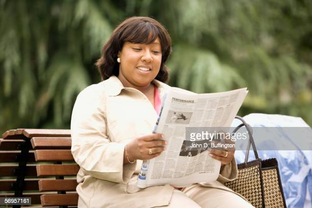 Woman sitting on bench reading newspaper