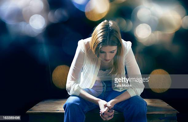 woman sitting on bench thinking with lens flare