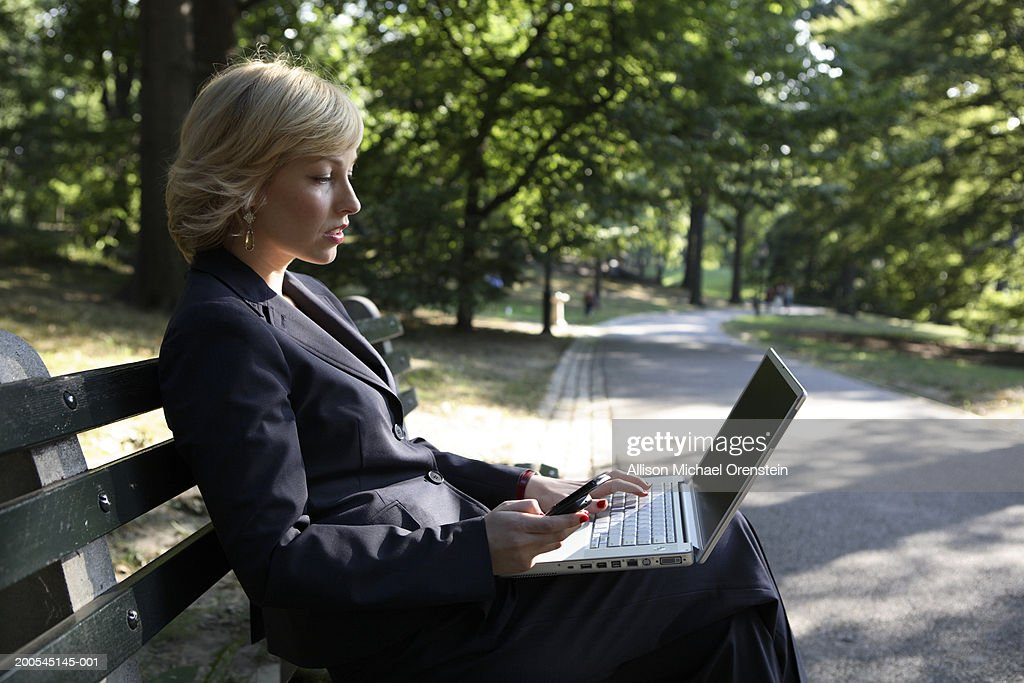 Woman sitting on bench with  laptop computer and cell phone in park : Stock Photo