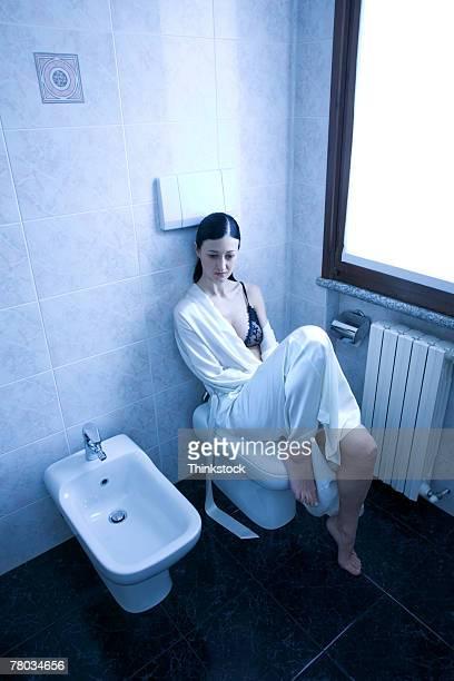 Woman sitting on bidet next to urinal