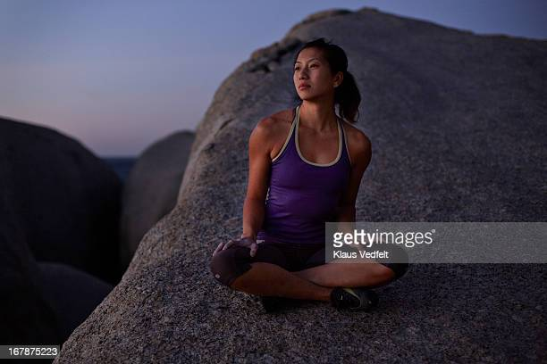 Woman sitting on big rock side looking at sunset