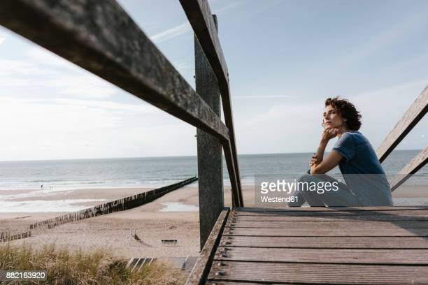 Woman sitting on boardwalk at the beach