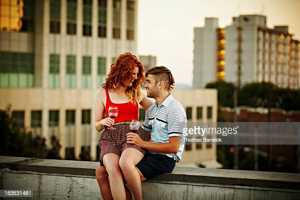 Woman sitting on boyfriends lap on edge of rooftop