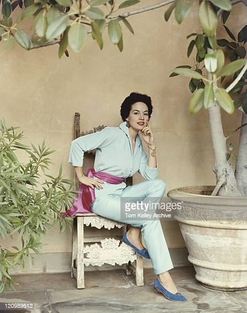 Woman sitting on chair beside huge pot plant, portrait