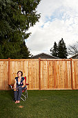 Woman sitting on chair in lawn by wooden fence
