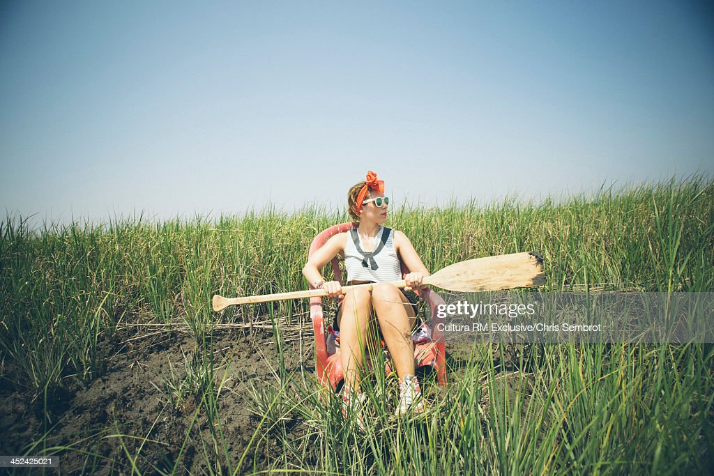 Woman sitting on chair on riverbank holding wooden oar : Stock Photo