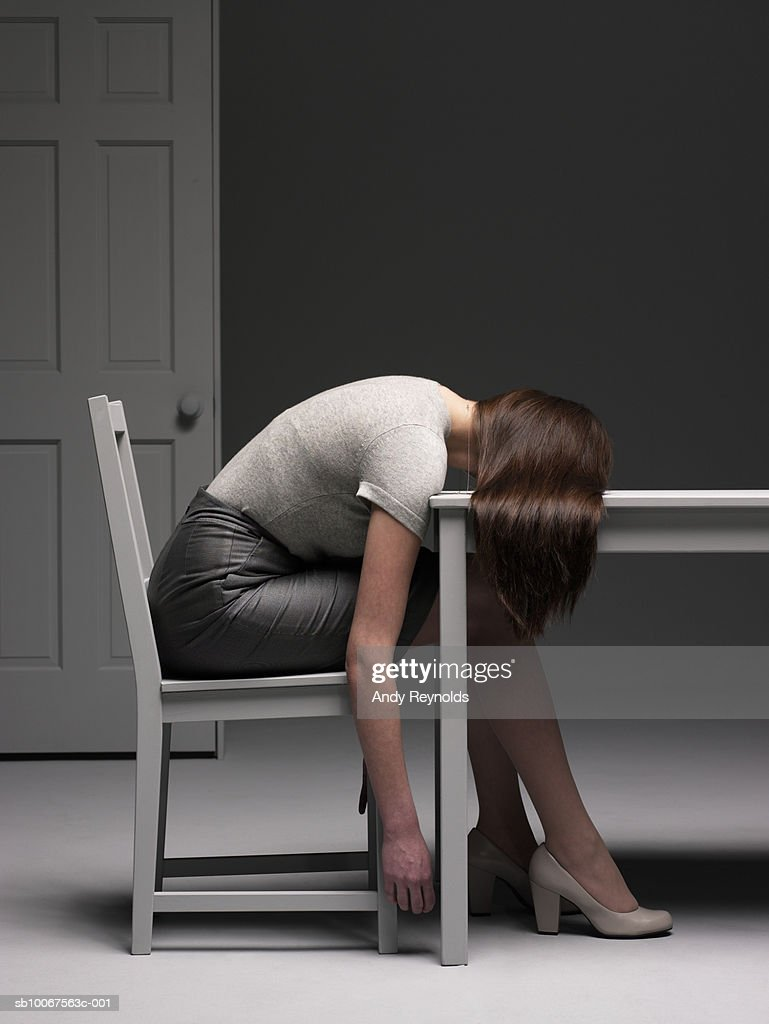 Woman sitting on chair resting head on table, side view : Stock Photo
