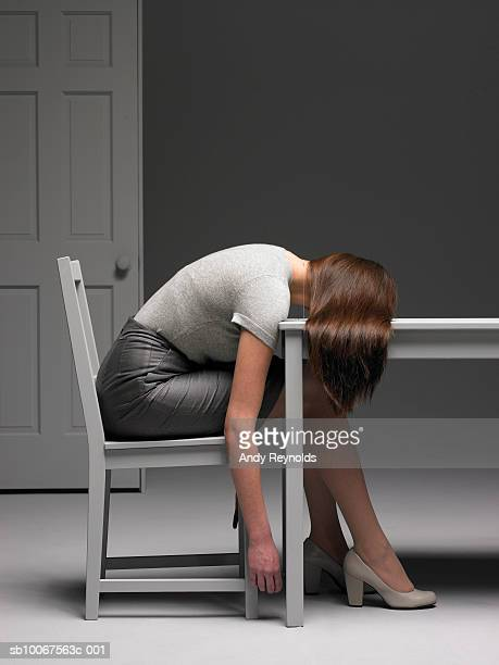 Woman sitting on chair resting head on table, side view