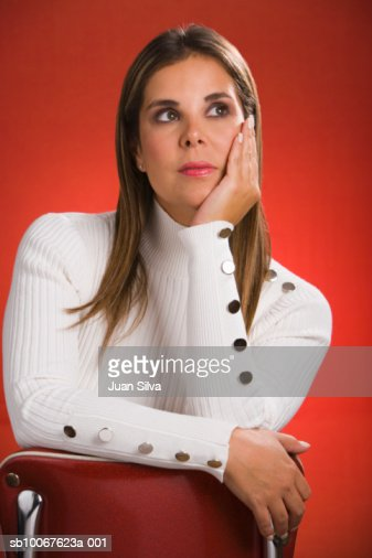 Woman sitting on chair with head in hand, looking away, close-up : Stock Photo