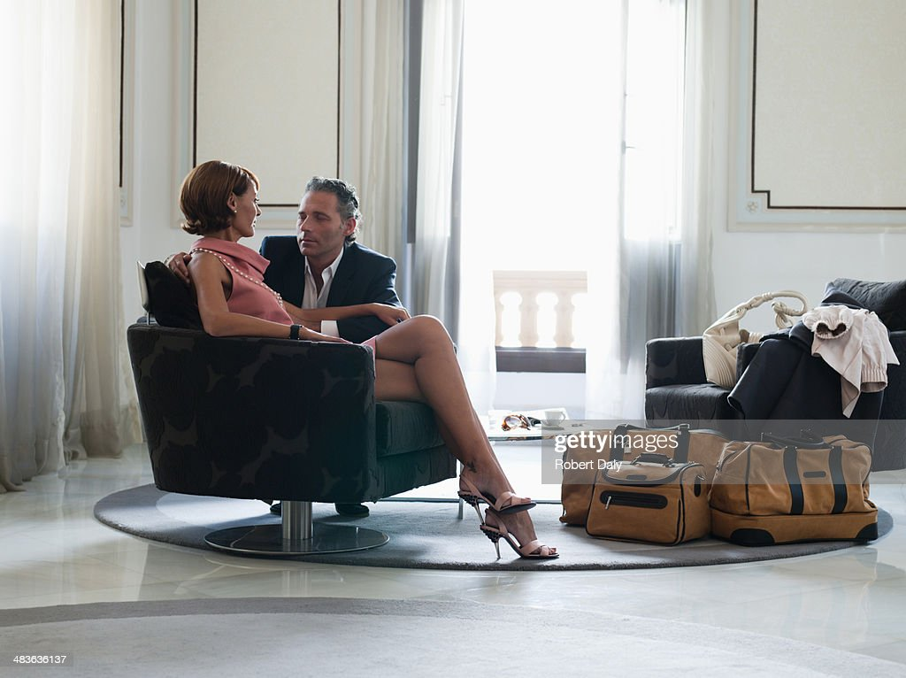Woman sitting on chair with man beside looking at man : Stock Photo