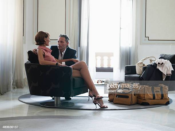 Woman sitting on chair with man beside looking at man