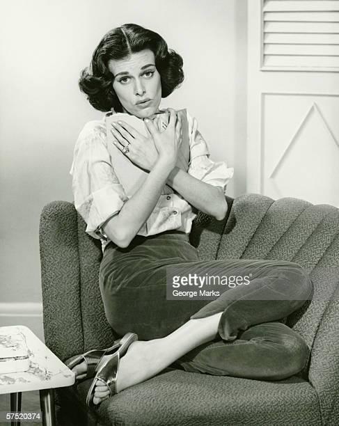 Donna seduta sul divano, cuddling libro (B & W), verticale